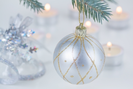 baubles: silver  christmas ball hanging on fir tree and candle lights defocused