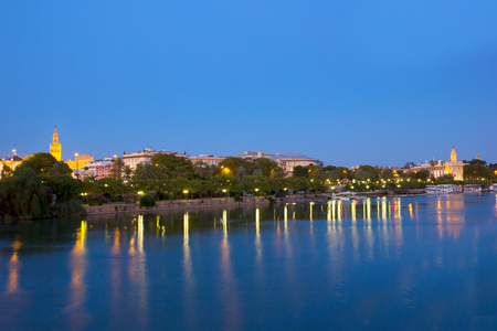 cityscape of Sevilla on river Guadalquivir at night, Spain Andalusia photo