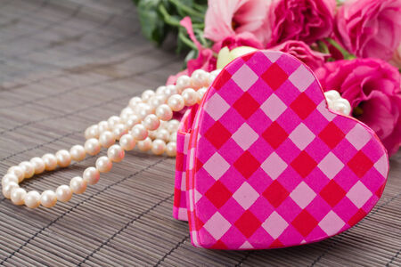 pink heart shaped  box with pearls and flowers photo