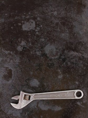 Adjustable wrench ob black metal background with copy space photo