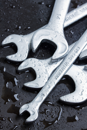 Set of wrenches on black metal in water drops photo