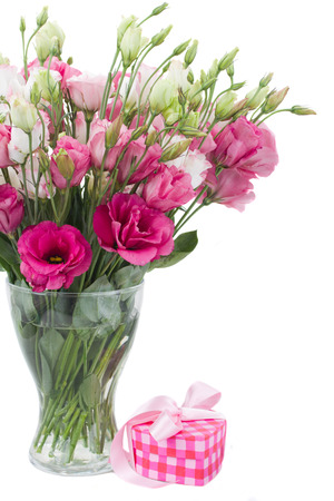 Pink eustoma flowers with  gift box with ribbon  isolated on white photo