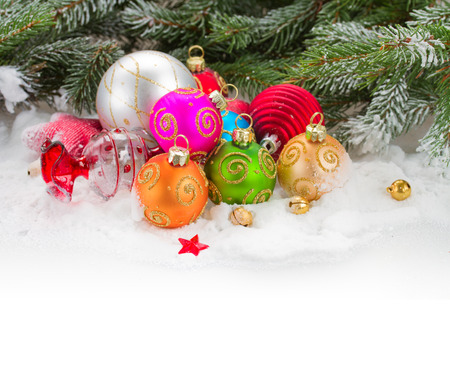 green fir tree and multicolored  christmas balls  on white snow photo