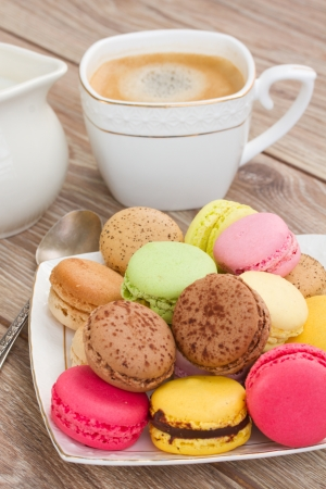 plate of multicolored macaroons with coffee  and on wooden table photo