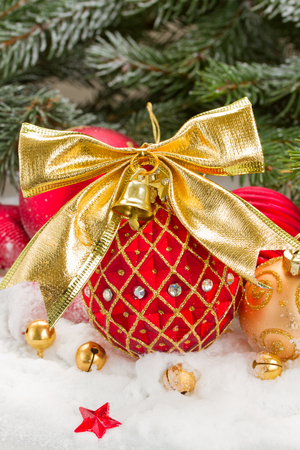 red  and gold christmas ball with bow in snow photo