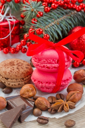 strawberry and chocolate macaroons  with christmas tree and decorations close up photo