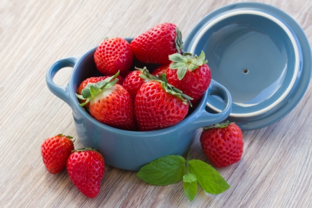 fresh strawberry in bowl  and on a kitchen table photo