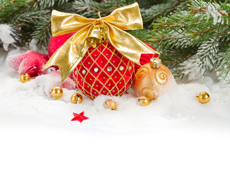 green fir tree and red christmas ball with golden bow   on white snow photo