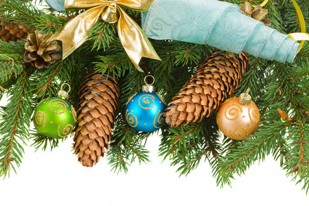 green fir tree and  christmas decorations with cones border on white background photo