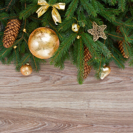 decorated with golden decorations green fir tree border on wooden background photo