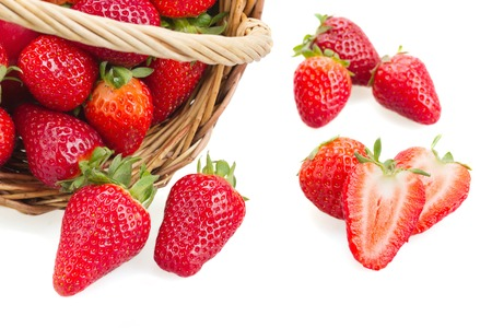 produce sections: Directly above shot of fresh strawberries and wicker basket over white background