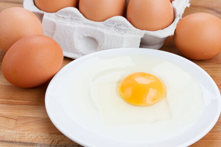 raw eggs and broken one in white plate photo