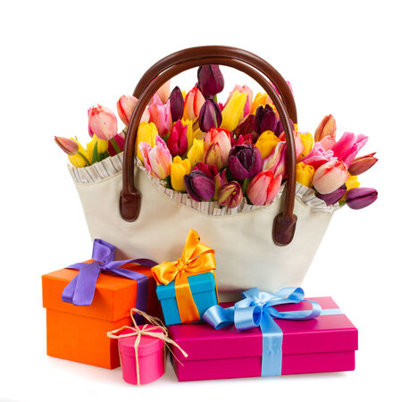 Bag   of spring  tulips flowers with gift boxes   isolated on white background photo