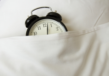 alarm clock sleeping in white linen bed