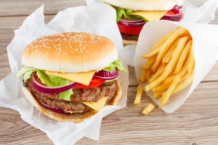 Big fresh  burger with french fries on wooden table