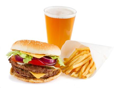 Hamburguesa con las patatas fritas y la cerveza aisladas sobre fondo blanco