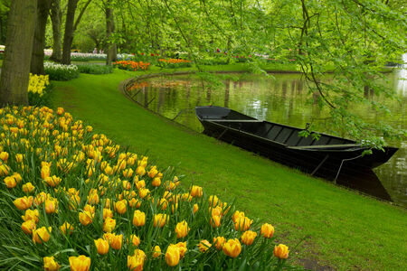 spring garden with canal and boat,   'Keukenhof', Holland Stock Photo - 24635279