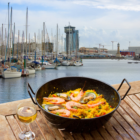 marisco: Seafood paella with glass of wine in seaside cafe,port of  Barcelona