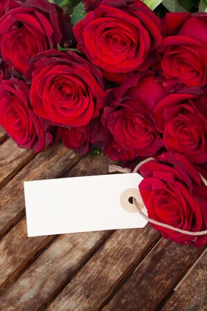 dark red roses  and tag  on wooden  table photo