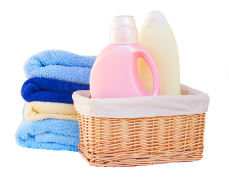Clothes with detergent  in basket isolated on white background photo