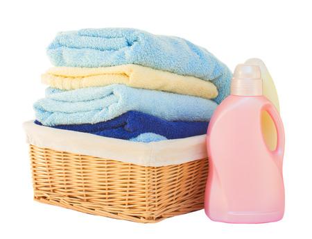白い背景で隔離のバスケットで洗剤と服