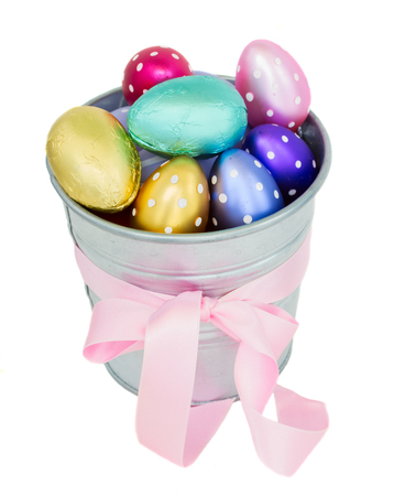 hatched: multicolored easter eggs in metal  pot with pink  bow isolated on white