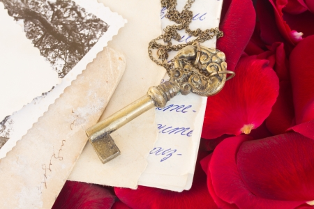 Key with old papers and  crimson  rose petals as a symbol of love photo