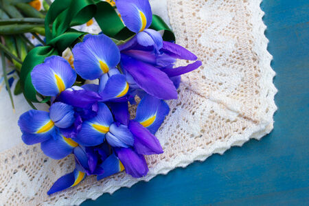 pile  of iris flowers laying on blue  table photo