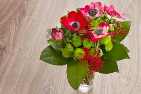 bouquet of  red anemone flowers on wooden table photo