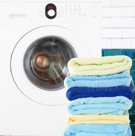launderette: pile of colorful  clean towels with washing machine in bathroom Stock Photo