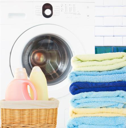 detersivi: Mucchio di asciugamani colorati con detersivo e lavatrice in bagno Archivio Fotografico