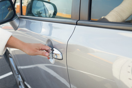 woman hand  opens  door of gray metalic car close up photo