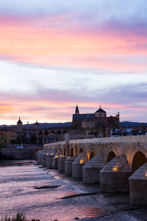 Mezquita and roman bridge at sunset, Cordoba, Andalusia, Spain photo