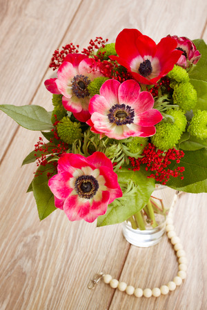 posy  of  red anemone flowers on wooden table photo