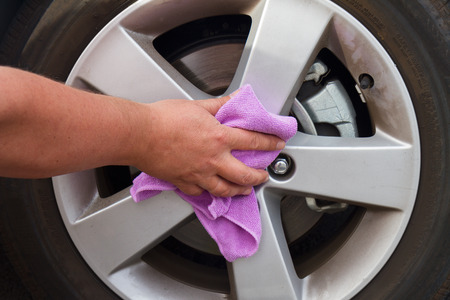 hand with cloth over coated wheel of car Stock Photo - 25736377