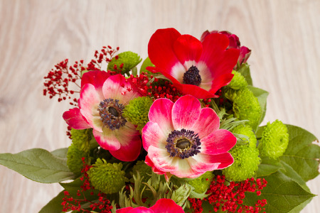 bouquet of  red anemone flowers on wooden table close up photo