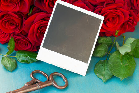 fresh red roses on wooden table with blank instant photos photo