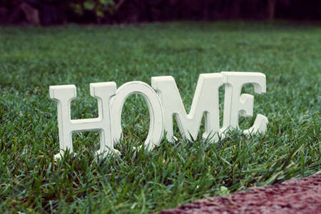 White letters Home in backyard green grass lawn photo