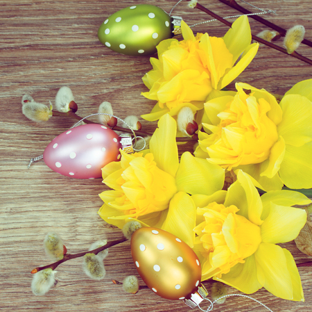 bouquet of yellow narcissus with catkins  and easter eggs on wooden table photo