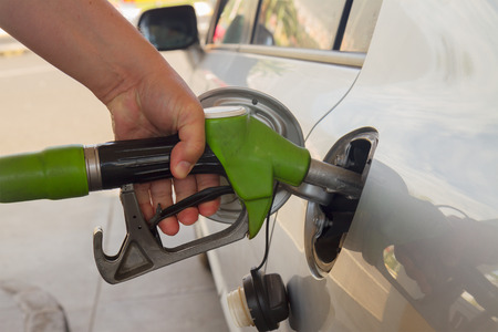 refilling: close up of hand with pump refilling car with fuel