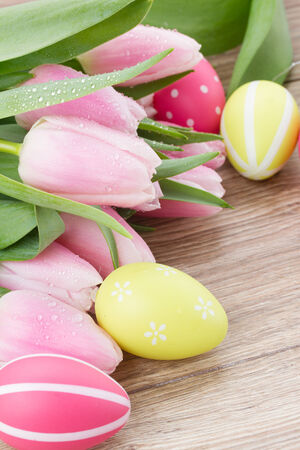 bouquet of fresh tulips with eggs for easter on wooden table photo