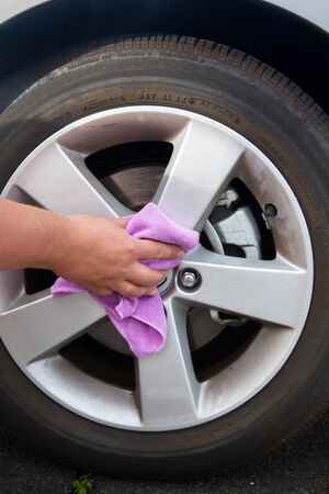 human hand with cloth over coated wheel of car photo