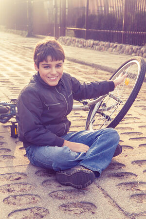 boy sitting on the ground with bicycle ,  retro toned photo