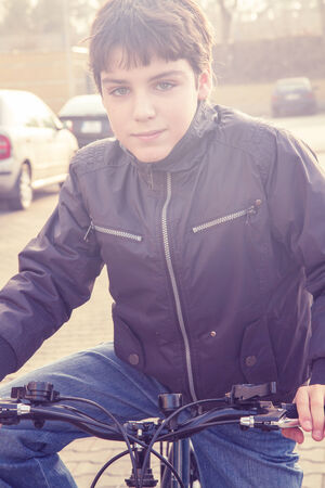 pretty young boy sitting on the  bicycle, retro toned Stock Photo - 26496398
