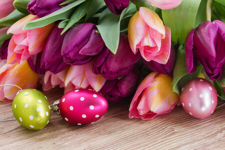 bouquet of spring tulips with eggs for easter on wooden table photo