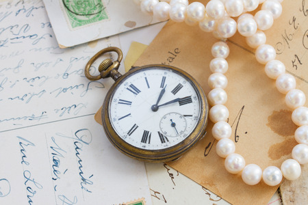 pile of old letters  with antique  clock and pearls photo