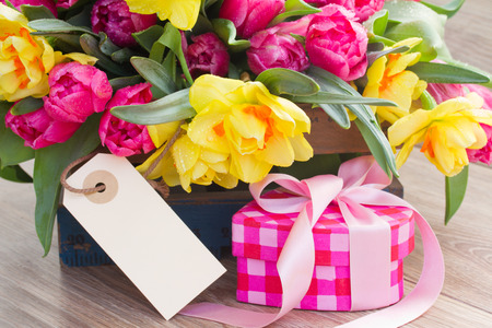 spring tulips and daffodil flowers with gift box and empty tag photo