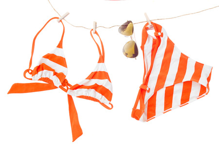 swimming suit with glasses hanging on rope  isolated on white background photo