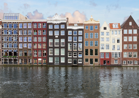 row of historic buildings over canal waters, Amsterdam, Netherlands photo