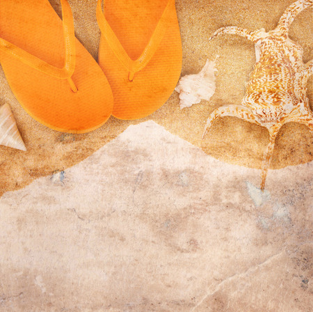 Old paper background with sandals and sea shells on sand photo